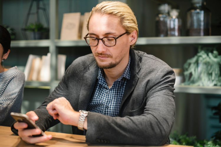 A man looking at his watch and a smartphone